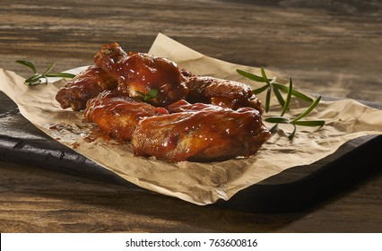 Made from Re-Plated Waste food – Fresh hot wings with red hot sauce and rosemary on paper wood board, wood table, angled view