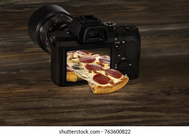 Made from Re-Plated Waste food – Fresh pepperoni pizza coming out of digital camera display, on dark wood table, concept image, angled view