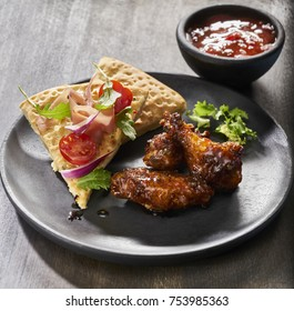 Made from Re-Plated Waste food – Hot chicken wings with sauce bowl and salmon focaccia sides on wood plate, angled view