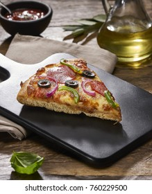 Made from Re-Plated Waste food – Pizza slices with pepperoni, peppers, olives, onions and cheese on gourmet plating, restaurant table, angled view