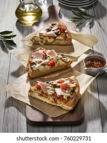 Made from Re-Plated Waste food – Pizza slices with mushrooms, tomatoes, olives, ham and cheese on gourmet plating, restaurant table, angled view