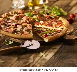 Made from Re-Plated Waste - Fresh sliced mixed pizza on wood board, wood table with pizza cutter, herbs, oil, blurred background, angled view