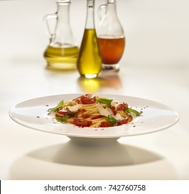 Made from Re-Plated Waste - Pasta dish with parmesan, tomato and basil on white plate, light table background with oil bottles, angled view