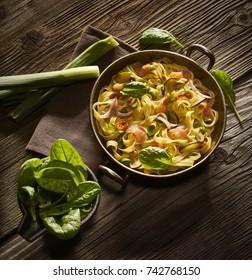 Made from Re-Plated Waste - Pasta dish with salmon, zucchini, peppers, spinach, herbs in metal pot, plating, dark background, top view