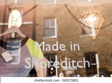 """Made in Shoreditch"" written in white ink on a shop window in Shoreditch (London).T-Shirt hanging inside and reflection of a building as background."