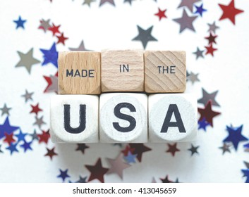 """MADE IN THE USA"" printed on wood blocks against white and metallic star confetti"
