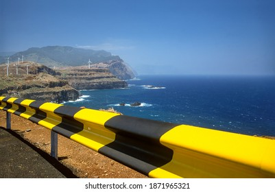 Madeira cliff with wind turbines and guard rail
