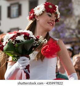 Madeira Flower festival (Festa da Flor). Closeup portrait of beautiful woman participant with flowers bouquet.