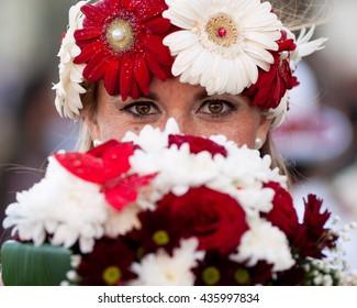 Madeira Flower festival (Festa da Flor). Closeup portrait of beautiful woman participant with flowers bouquet. Carnival in Madeira.