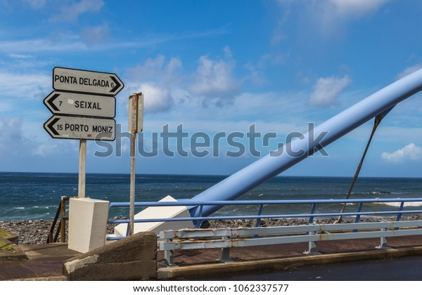 Madeira landscape of the Atlantic Ocean coast with balustrades of the bridge and signpost showing directions to places: Ponta Delgada, Seixal, Porto Moniz under the blue cloudy sky on a sunny day.