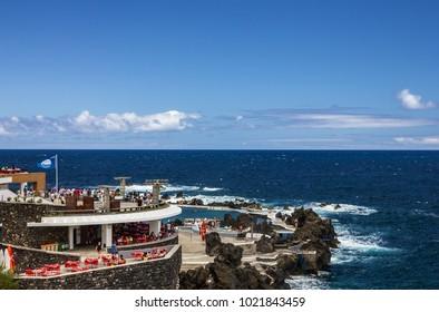 MADEIRA, PORTUGAL - JAN 4, 2018: Tourists in natural pools in resort Portu Moniz, Madeira island, Portugal