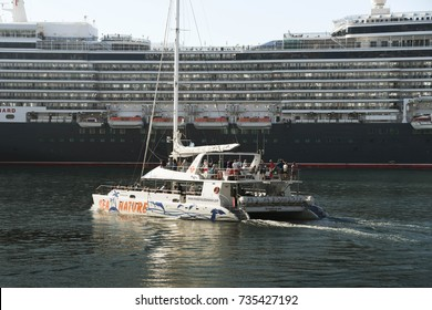 Madeira, Portugal - September 2017: A catamaran leaves the harbor taking tourists on an excursion, with the Cunard cruise liner QE2 in the background