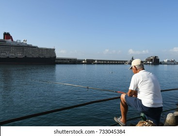 Madeira, Portugal - September 2017: Man fishing in the city's harbour with the cruise liner, the QE2, in the background