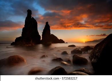 Madeira seascape dawn. Long exposure from the rocky shore of the coast of Ribeira da Janela, Madeira island. Dramatic sunrise seascape, misty rocks hit by waves. Two steep cliffs against rising sun.