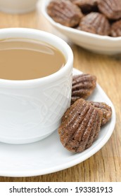 madeleine cookies and a cup of coffee with milk on a plate on the wooden table