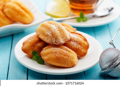 Madeleine - homemade traditional French small cookie on light blue background.