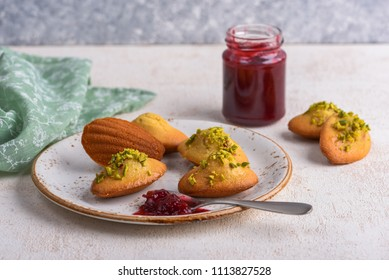 Madeleines with cherry jam and pistachio