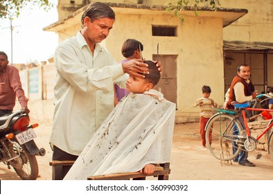 MADHYA PRADESH, INDIA - DEC 29: Unidentified boy sitting in chair of rural barbershop and doing new hairstyle by a barber on December 29, 2012 in Chitrakoot. Populatation of Chitrakoot is 22,294