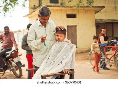 MADHYA PRADESH, INDIA - DEC 29: Unidentified preschool child with unhappy face doing new hairstyle by village barber on December 29, 2012 in Chitrakoot. Populatation of Chitrakoot is 22,294