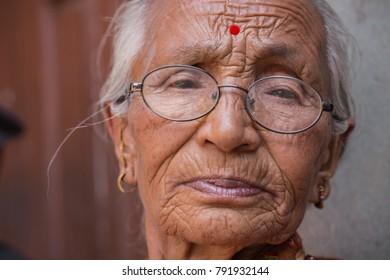 Madhyapur Thimi, Bhaktapur District, Nepal. 4 Jun 2017. Documentary. Portrait of an unidentified nepalese elderly woman wearing glasses.