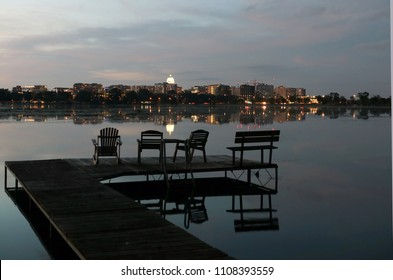 Madison downtown skyline with Wisconsin State Capitol building dome as seen from across lake Monona bay. After sunset sky and downtown skyline reflected in a water. Pier with chairs on a foreground.
