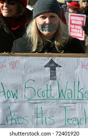 MADISON, WI - FEB 19: Unidentified woman protests WI Budget Repair Bill on February 19, 2011 on the capitol square in Madison, WI.  The woman wears tape on her mouth representing having no voice.