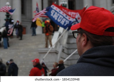Madison, WI / USA - November 14, 2020: A white man with a Keep America Great hat stands in the Stop the Steal Protest outside of the Madison Capitol building in Wisconsin.