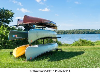 Madison, Wisconsin / United States of America - August 8th 2019 : A full rack of colorful canoes, sitting near a lake on a sunny summer day.