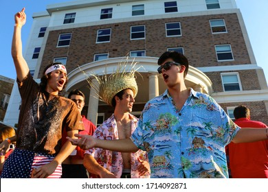 Madison, Wisconsin / United States - September 20, 2017: College students enjoy their game day party while having a good time on the lake. They wear their school color red while dancing and singing.
