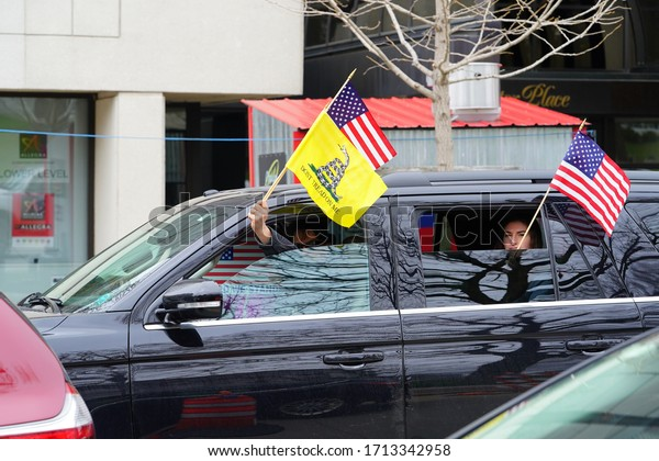 Madison, Wisconsin / USA - April 27th, 2020: Wisconsinites in cars, trucks, and SUVs rallied at the Capitol of Wisconsin gridlocking the streets in protest against safer at home during the COVID-19.