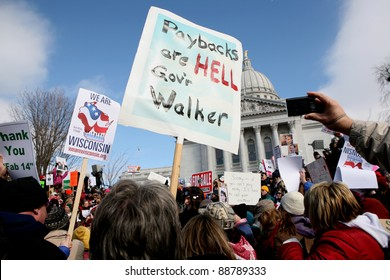 MADISON,WI - FEB 19: Signs are lifted in front of Wisconsin's Capitol protesting Gov Scott Walker on Feb 19, 2011 in Madison, WI.  The Wisconsin drive to recall Walker starts Nov 15.