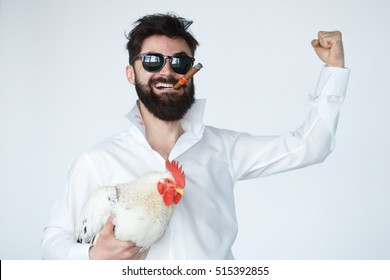 madness and people concept - crazy man smiling while holding a chicken over white background