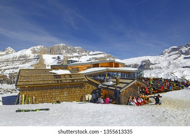 MADONNA DI CAMPIGLIO, ITALY - MARCH 21, 2019: Tourists in front of mountain hut Chalet Fiat, Ski Resort Brenta Dolomites, UNESCO World Heritage Site, Trento Province, Trentino Region, Upper Adige