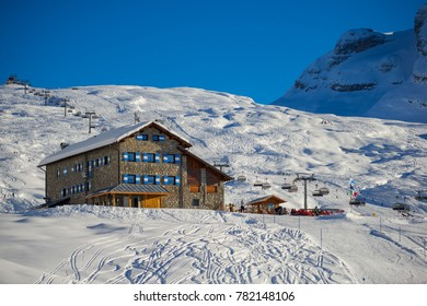 MADONNA DI CAMPIGLIO, ITALY-21 November 2014:Panoramic winter landscape of Dolomiti mountain and Mountain shelter in Madonna di Campiglio. The ski slope and skiers at Passo Groste ski area