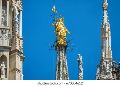 The Madonnina atop Milan Cathedral at the height of 108.5 m in Milan, italy. Golden Madonna close-up on the blue sky background. Milan Cathedral or Duomo is the main tourist attraction of Milan.