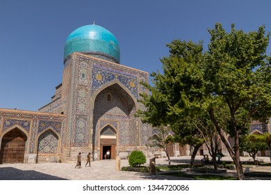 Madrasah Tillya-Kari view from the yard. In the courtyard of the Madrasah with trees. Inside the Madrasah on Registan square in Samarkand. Ancient Madrasah in Uzbekistan. Sunny summer day.