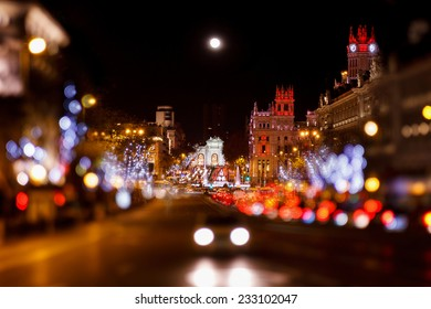 Madrid at Christmas. Rays of traffic lights on Cibeles square, Cibeles fountain in front of the The City Hall or the former Palace of Communications in Madrid, Spain.