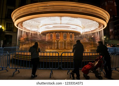 MADRID - DECEMBER 28, 2017: Tourists and locals enjoy a ride at a Christmas carousel in the Plaza Mayor in Madrid, Spain.