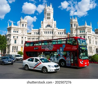 MADRID JULY 2, 2014  Cibeles Palace (Palacio de Cibeles): City Hall of Madrid (formerly Palace of Communication) and tour bus. Iiconic monument of the city.  In Madrid, Spain on July 2, 2014.