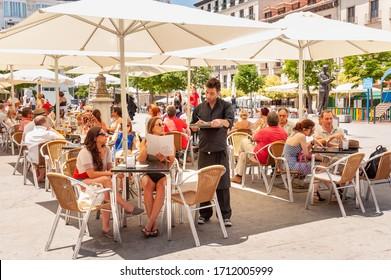MADRID - JUNE 4, 2012: People ordering drinks at bar tables on Plaza de Santa Ana, Barrio de las Letras