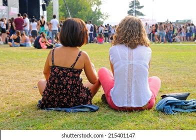 MADRID - SEP 14: Two girls sitting on the grass at Dcode Festival on September 14, 2013 in Madrid, Spain.