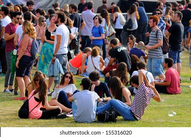 MADRID - SEPT 14: People sitting on the grass at Dcode Festival on September 14, 2013 in Madrid, Spain.