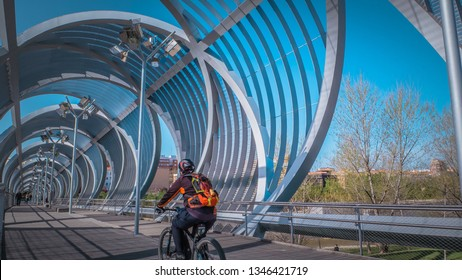 Madrid / Spain - 03 17 2019: People walk inside the Arganzuela modern metal footbridge outdoors at Madrid Rio green park across the Manzanares river downtown Madrid on a warm spring day.