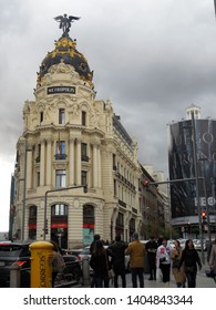 Madrid / Spain - 04/07/2019: Edificio Metrópolis is Beaux-Arts office building in Madrid, Spain, at the corner of the Calle de Alcalá and Gran Vía. Overcast sky, and pedestrians on the street.