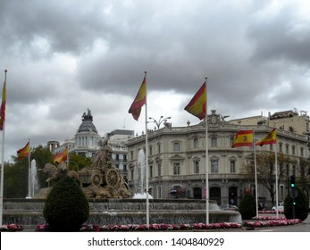 Madrid / Spain - 04/07/2019: Plaza de Cibeles Exterior, with fountain, statue, traffic circle, cloudy sky, and Spanish flags.