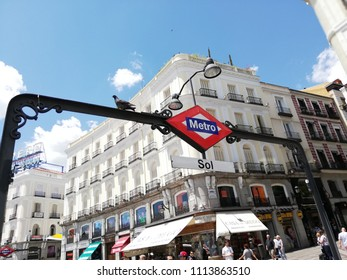 Madrid / Spain - 06 13 2018: Sol metro sign at Puerta del Sol central square downtown Spanish capital Madrid on sunny day with blue sky. People, tourists are walking downtown Madrid.