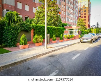 Madrid, Spain; 08 11 2018: A photo of a nice sidewalk on Yerma street just in front of a business center. In the picture there are a group of residential buildings, cars, trees, and flower pots.