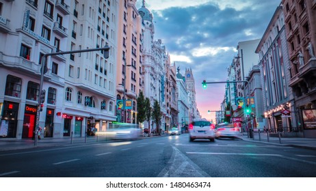 Madrid / Spain - 08 11 2019: Famous view of Gran Via main broadway road in the downtown of Madrid, Spain with Telefonica building and traffic cars moving in motion blur during sunrise / sunset.