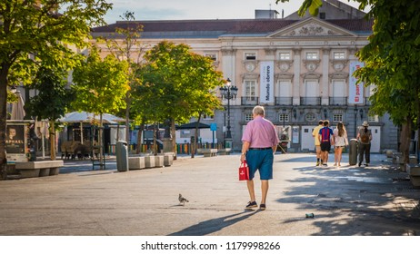 Madrid / Spain - 08 16 2018: People walking towards Spanish Theater or Teatro Español at the Plaza de Santa Ana or Saint Anne square downtown Madrid, Spain in Literary Quarter.
