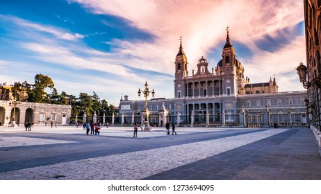 Madrid / Spain - 12 26 2018: People, tourists at Plaza de Armeria or Armory square with royal vintage lantern light in front of the Royal Palace and Almudena cathedral downtown Madrid at sunset